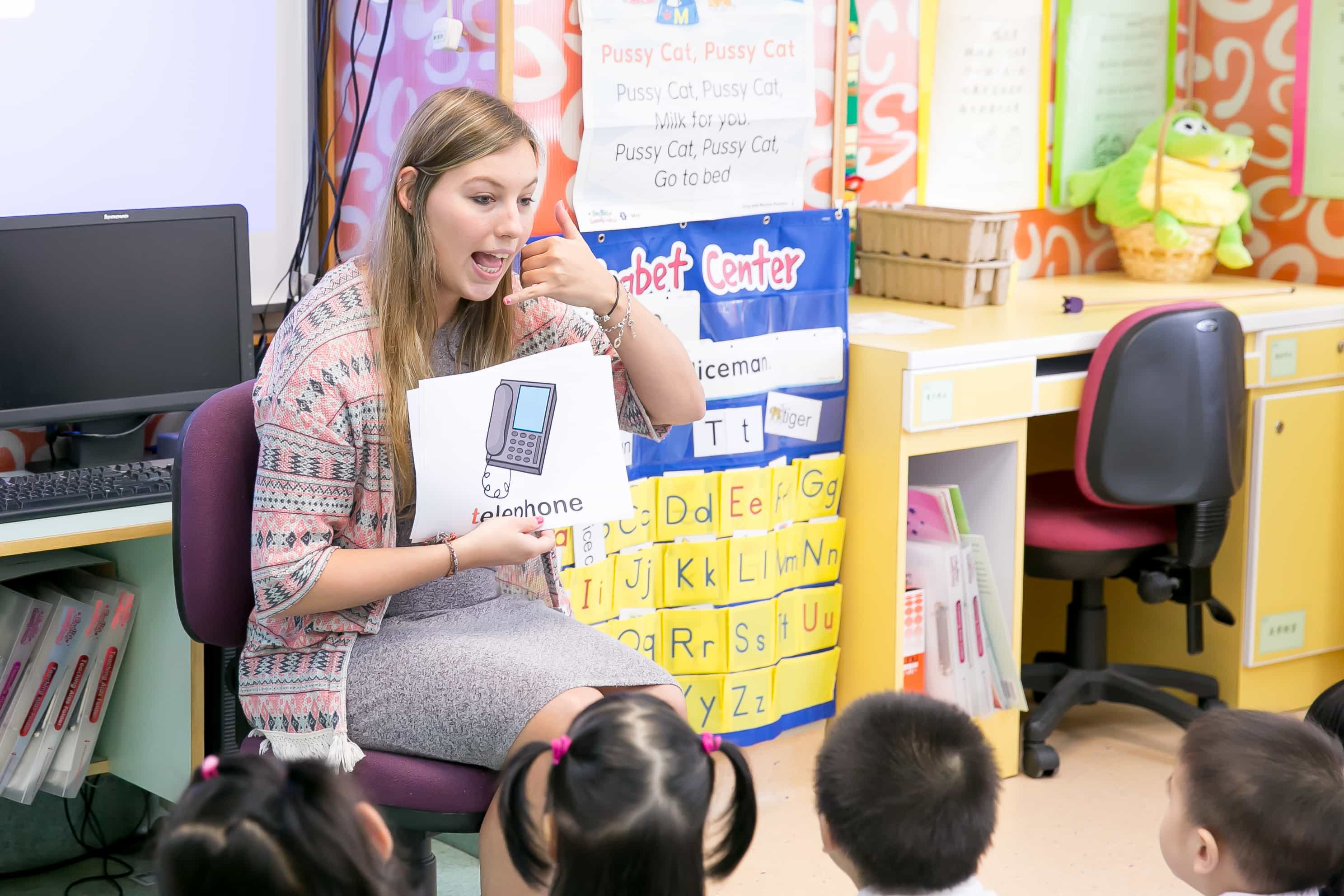 a TEFL teacher in the classroom explaining children the word telephone
