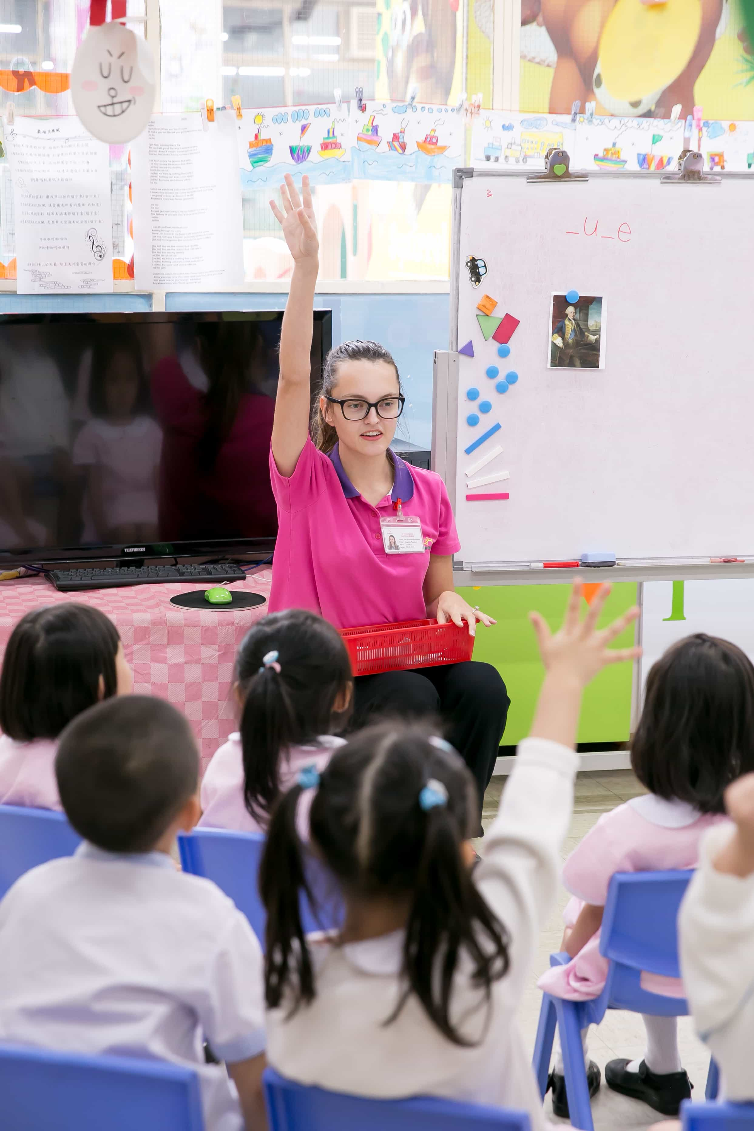 a young TEFL teacher is encouraging children to work at the lesson